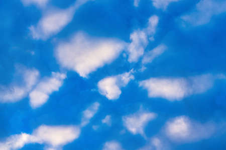 Stunning clouds in blue sky, illuminated by rays of sun at sunset to change summer weather. Soft focus, motion blur multicolored cloudscape abstract background. Stockfoto