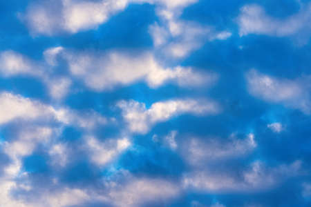 Amazing clouds in blue sky, illuminated by rays of sun at sunset to change weather. Soft focus, defocus, motion blur multicolored cloud scape abstract background.