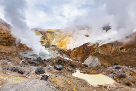 Beautiful mountain landscape, crater of active volcano: fumarole and hot spring, geothermal gas-steam activity, lava plain. Amazing volcanic landscape, travel destinations for hike, mountain climbing.
