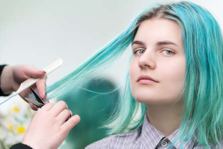 Hairdresser cutting with scissors long green hair of young woman. Hair care in professional beauty salon.
