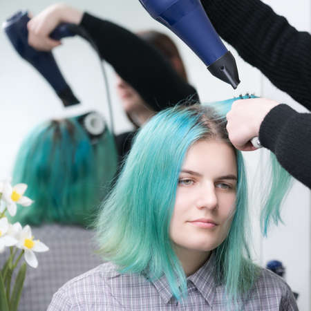 Portrait of beautiful young woman with long green hair while drying and styling hair in beauty salon. Brunette hairstylist dries customer hair with blue hairdryer and hairbrush.