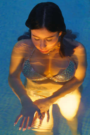 Glamorous brunette in swimsuit swims in geothermal water in pool at spa. Photo at dusk, womans curvy body is illuminated under water by night lights in pool. Soft selective focus on models eyes. Stockfoto