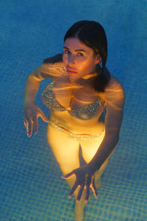 Beautiful woman in swimsuit swimming in water in pool at geothermal spa. Photo at dusk, womans curvy body is illuminated under water by night lights in pool. Medical stay at balneotherapy resort.
