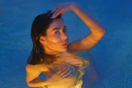 Brunette in swimsuit relaxation in geothermal water in pool at balneotherapy spa, hot springs resorts. Womans body illuminated under water by night lights in pool. Soft selective focus on model eyes.
