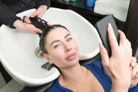Brunette woman looks at smartphone while hairdresser is busy washing her hair at beauty salon. Hairstylists hands wash long hair of customer with shampoo in sink for shampooing in beauty salon.