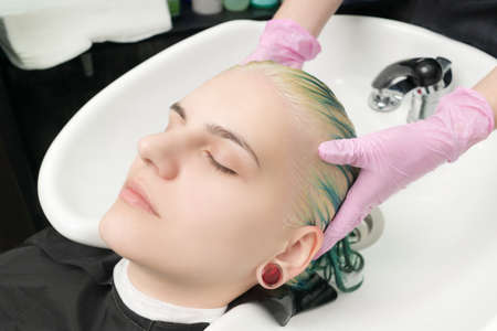 Hairdresser washes and lathers clients head with hair conditioner while washing head in special sink in beauty salon. Caucasian young woman is relaxed and lies with her eyes closed during process.