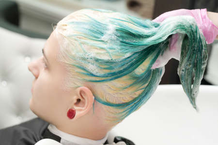 Washing emerald hair color of young woman with shampoo in sink. Working hairdresser in pink protective gloves in professional hair salon. Stockfoto