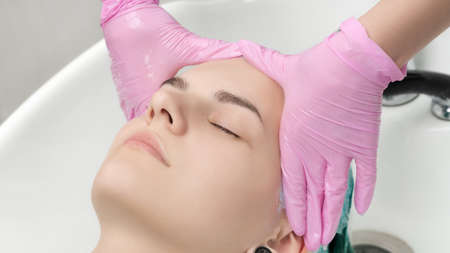 Head of young woman with closed eyes in sink in hair salon. Hairdresser hands in pink protective gloves washing hair in professional beauty salon.