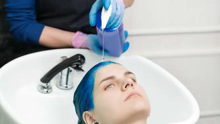 Hairstylist hands in gloves squeezes shampoo from tube into head young woman with blue hair while washing hair in special sink and shower at beauty salon after hair dyeing process. Stockfoto