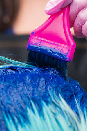 Hairdresser in protective glove using magenta brush while applying blue paint to emerald hair color, during process of dyeing hair in stylish color at professional hair salon.