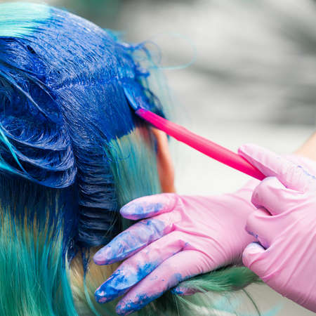Side view of process of dyeing hair in stylish color. Hairdresser in pink protective glove using magenta brush while applying blue paint to woman customer with modern emerald hair color.