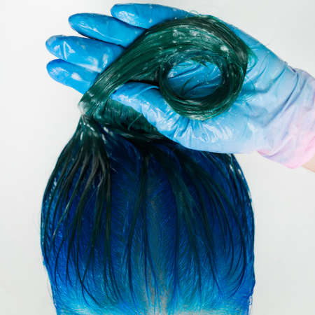 Washing of woman hair with conditioner shampoo in sink with special shower. High-angle shot of beautician in gloves washes customer long hair sapphire color after dyeing hair process in professional beauty salon.