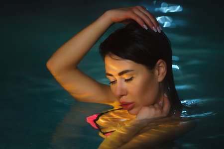 Night portrait of brunette woman swimming in pool with hot mineral water in balneotherapy spa. Beautys face is illuminated by night lights in pool. Selective soft focus on female eyes. Stockfoto