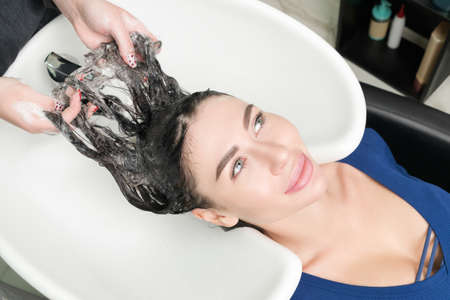 Hairstylists hands wash long hair of Caucasian brunette woman with shampoo in professional sink for shampooing in beauty salon.