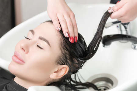 Hairstylists hands wash long hair of glamour brunette woman with shampoo in professional sink for shampooing in beauty and hair salon.