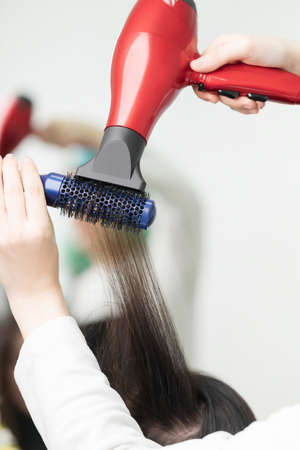 Hands of hairstylist drying brunette hair of client using red hairdryer and blue comb. Occupation in professional beauty salon.