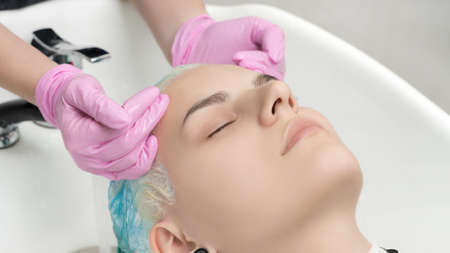 Hairstylist hands in pink gloves washing emerald hair color in professional beauty salon. Head of young woman with closed eyes in special sink hair salon.