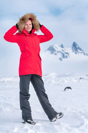 Woman climber dressed in red winter windproof jacket and holds hood up over his head, standing in snow against backdrop of rocky mountains on horizon. Attractive smiling sporty woman posing outdoors Stockfoto