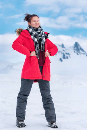 Sporty woman traveler dressed in red winter windproof jacket, black and white scarf around neck, gray sports pants and trekking boots standing in mountains in cold winter weather. Stockfoto
