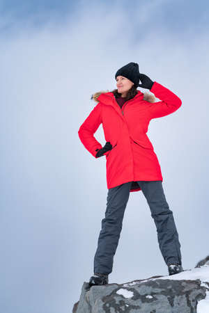 Young woman standing on top of mountain peak on background of sky with dramatic clouds. Smiling woman dressed in red windproof jacket, sports pants and trekking boots. Travel concept, copy space. Stockfoto
