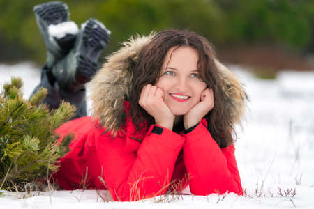 Nice brunette woman with long curly hair lies on winter snow in coniferous forest, smiling and looking to side. Young Caucasian woman dressed in red windproof jacket and trekking boots.