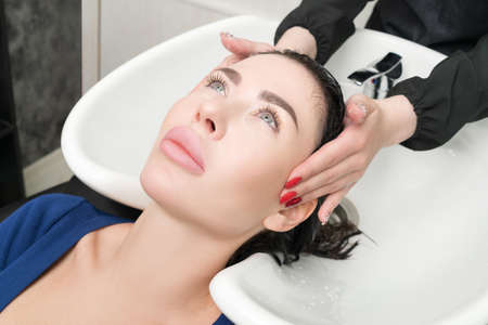 Professional hairstylists hands wash long hair of brunette woman with shampoo in sink for shampooing in professional hair salon.