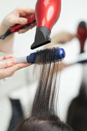 Hands of beautician drying long brunette hair of client using red hair dryer and hairbrush in professional beauty salon.