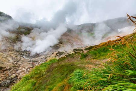 Thrilling view of volcanic landscape, aggressive hot spring, erupting fumarole, gas-steam activity in crater of active volcano. Scenery mountain, travel destinations for hike, active vacation. Stockfoto