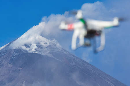 Flying drone quadcopter UAV aerial photography in sky on background volcano eruption, mount peak erupting ashes, gas from active crater. Focus on mountain. Kamchatka Peninsula, Russia - Oct 1, 2016