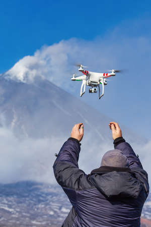 Male launches flying drone quadcopter UAV with digital camera on background of volcano eruption, mount peak erupting ashes, volcanic gas from active crater. Kamchatka Peninsula, Russia - Oct 1, 2016