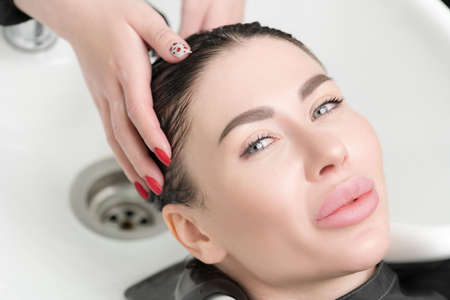 Hairdressers hands wash long hair of beautiful brunette woman with shampoo in special sink for shampooing in hair and beauty salon. Stockfoto