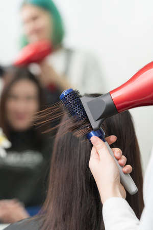 Hands of hairstylist dries brunette hair of client using red hair dryer and blue comb in professional beauty salon.