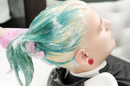 Professional beauty salon: hairstylist hands washing green hair of young woman with shampoo in sink. Head of young woman lies with closed eyes.