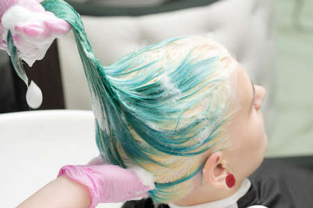Washing green hair color of young woman with shampoo in sink. Working hairdresser in pink protective gloves in beauty salon.