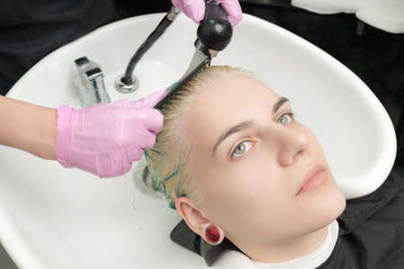 Professional hairdresser in protective glove combing green hair of customer, while washing hair in shower in special beauty salon sink. Stockfoto