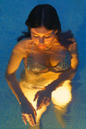 Pretty brunette in swimsuit relaxation in hot mineral water in pool at spa, hot springs resorts. Womans curvy body is illuminated under water by night lights in pool. Soft selective focus on eyes