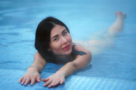 Adult brunette relaxation lies in geothermal water in pool at spa resort and looking at camera. Soft selective focus on models eyes. Stockfoto