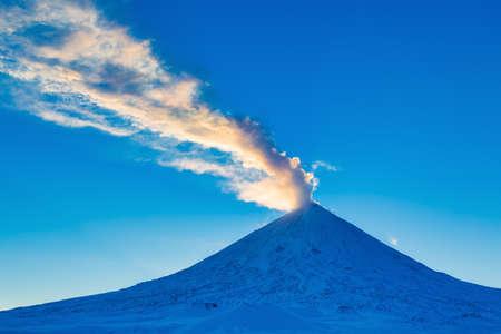 Winter eruption active Klyuchevskoy Volcano at beauty golden hour. Plume of gas, ash from crater, illuminated rays setting sun. Eurasia, Russia, Kamchatka Peninsula, Klyuchevskaya Group of Volcanoes. Stockfoto