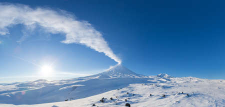 Winter volcanic landscape, panoramic view of eruption active volcano plume gas, ash from crater in sunny day with blue sky. Kamchatka Peninsula, Klyuchevskaya Sopka, Klyuchevskaya Group of Volcanoes.
