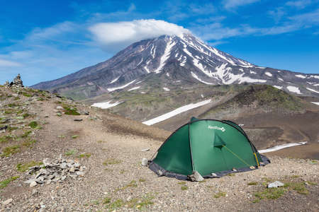 Green tourist tent Red Fox for camping and travel standing in mountain on background of volcanic landscape - cone of Koryak Volcano, blue sky with clouds. Kamchatka Peninsula, Russia - August 19, 2015