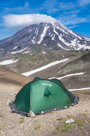 Green tourist tent Red Fox for camping and travel standing in mountain on background of beautiful volcanic landscape - cone of Koryak Volcano, blue sky with clouds. Kamchatka, Russia - August 19, 2015 Redactioneel