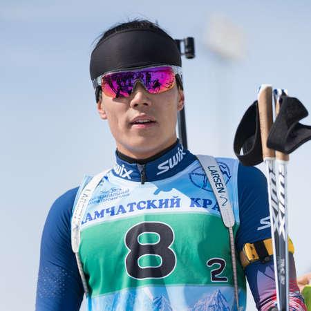 Portrait Korean sportsman biathlete Yang Seon Jik South Korea at finish after rifle shooting and skiing. Junior biathlon competitions East of Cup. Kamchatka Peninsula, Russian Far East - Apr 14, 2019.