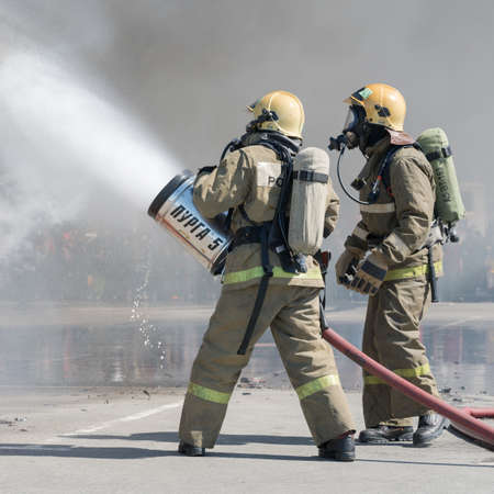 Two firefighters extinguishes fire from fire hose, using firefighting water-foam barrel with air-mechanical foam. Professional holiday Firefighters Day. Kamchatka Peninsula, Russia - April 27, 2019.