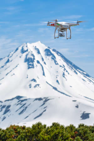 Tech drone quadcopter UAV flying in blue sky on background rocky volcano peak, filming aerial video and photo world around from birds eye view. Kamchatka Peninsula, Russia - June 18, 2017