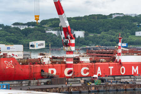 Crane unloading container cargo ship Sevmorput Rosatomflot - Russian nuclear-powered icebreaker lighter aboard ship carrier. Terminal commercial seaport. Kamchatka Peninsula, Russia - August 27, 2019.