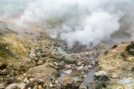 Breathtaking view of volcanic landscape, erupting fumarole, aggressive hot spring, gas-steam activity in crater of active volcano. Dramatic mountain landscape, travel destinations for active vacation.
