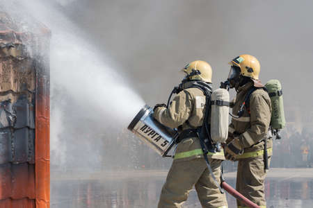 Firefighters extinguishes fire from fire hose, using firefighting water-foam barrel with air-mechanical foam during professional holiday Firefighters Day. Kamchatka Peninsula, Russia - April 27, 2019.