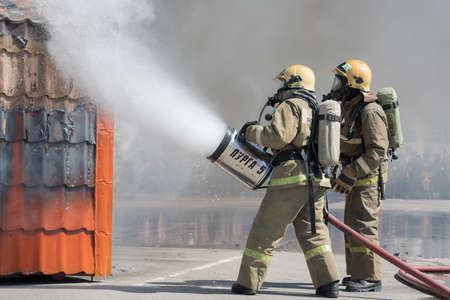 Firefighters extinguishes fire from fire hose, using fire-fighting water-foam barrel with air-mechanical foam. Professional holiday Firefighters Day. Petropavlovsk-Kamchatsky, Russia - April 27, 2019.