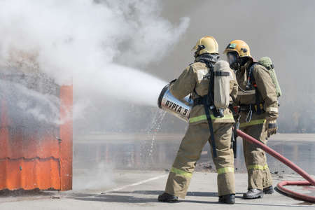 Firefighters extinguishes fire from fire hose, using firefighting water-foam barrel with air-mechanical foam. Professional holiday Firefighters Day. Petropavlovsk-Kamchatsky, Russia - April 27, 2019.