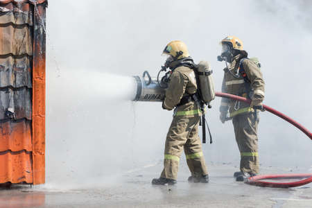 Firefighters extinguishing fire from fire hose, using firefighting water-foam barrel with air-mechanical foam during professional holiday Firefighters Day. Kamchatka Peninsula, Russia - April 27, 2019 Redactioneel